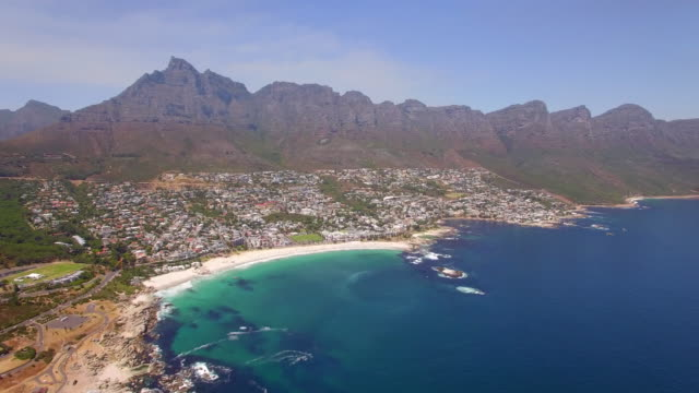 Aerial travel drone view of Camps Bay beach, Cape Town, South Africa.