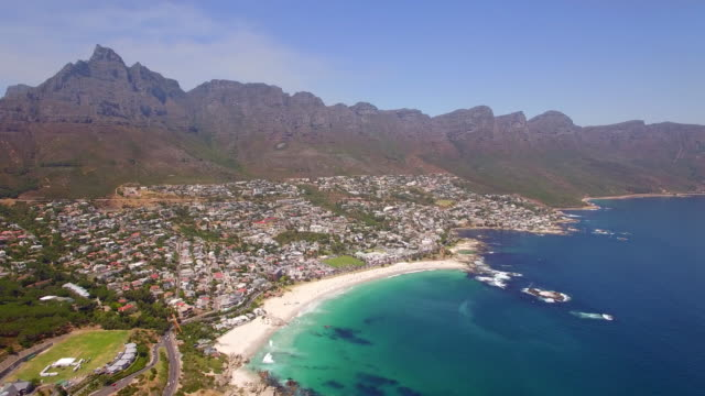 aerial travel drone view of camps bay beach, cape town, south africa. - città del capo video stock e b–roll