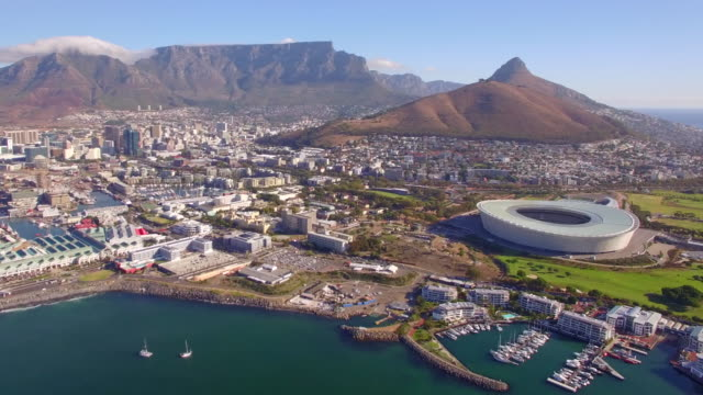 vidéos et rushes de aerial travel drone view of cape town, south africa with table mountain and stadium. - république d'afrique du sud