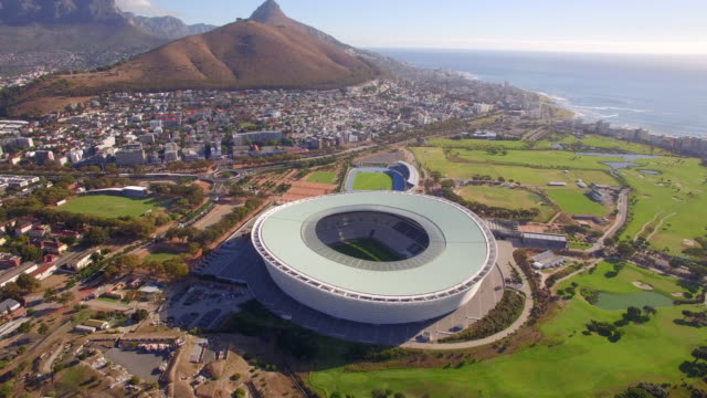 vídeos de stock, filmes e b-roll de aerial travel drone view of cape town, south africa with table mountain and stadium. - porto distrito