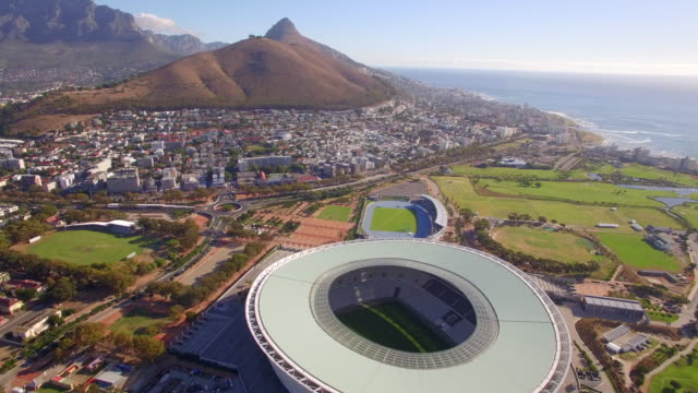 Aerial travel drone view of Cape Town, South Africa with Table Mountain and stadium.