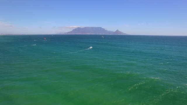 Aerial travel drone view of Table Mountain and Table Bay and kiteboarders from Bloubergstrand, Cape Town, South Africa.