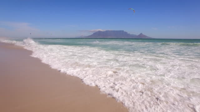 Aerial travel drone view of Table Mountain and Table Bay and kiteboarders from Bloubergstrand, Cape Town, South Africa. - Time-Lapse
