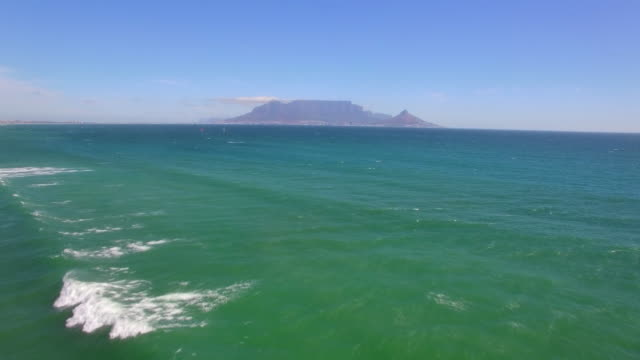 vídeos de stock, filmes e b-roll de aerial travel drone view of table mountain and table bay from bloubergstrand, cape town, south africa. - península