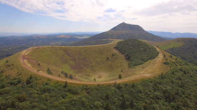 vidéos et rushes de aerial travel drone view of the puy de dome, lava dome volcano in france. - volcan
