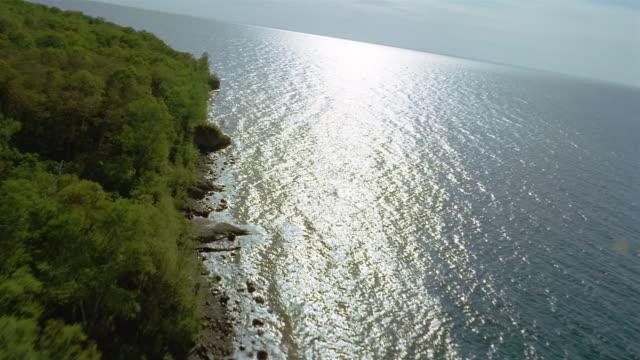 aerial tree-lined shore of lake superior/ sunlight reflecting off water/ rocky coastline/ minnesota - lago superiore video stock e b–roll