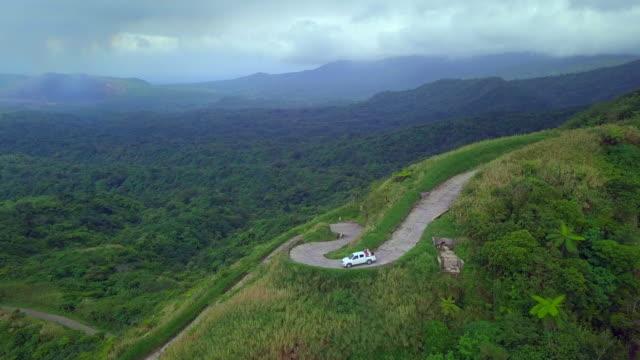 aerial: truck driving down steep mountain road in espiritu santo, vanuatu - lush stock videos & royalty-free footage