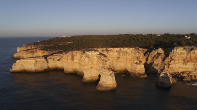vídeos de stock e filmes b-roll de aerial turning view of waves splashing on sea arch / praia de marinha, faro, portugal - penhasco caraterísticas do território