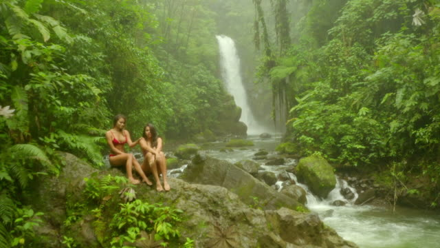 aerial: two beautiful young women in bikini sitting on rock in stream - costa rica video stock e b–roll