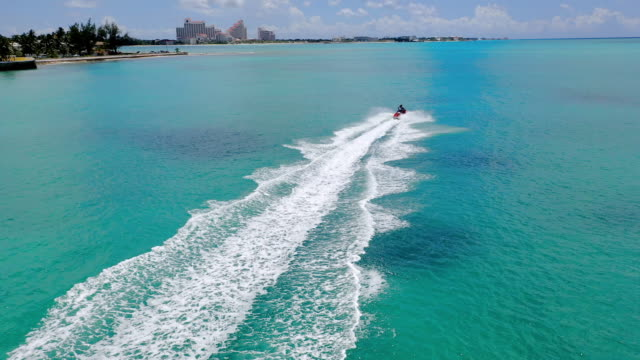 aerial: two people on one jet ski riding through beautiful blue tropical water  - nassau, bahamas - bahamas stock videos & royalty-free footage