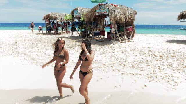 vídeos y material grabado en eventos de stock de aerial: two sexy young women on small island surrounded by bright blue water - rodear