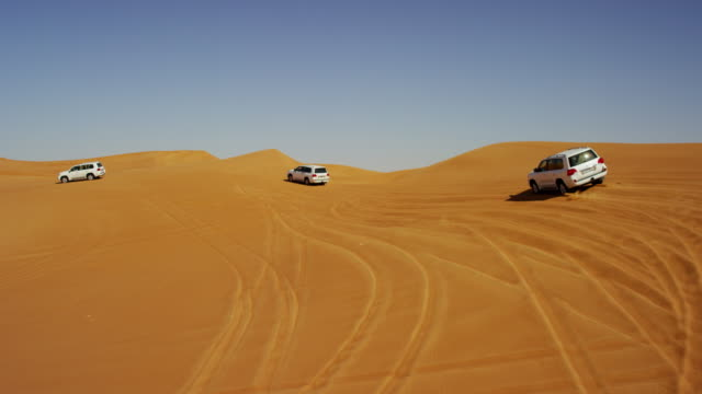 aerial uae drone off road vehicles desert safari - sand dune stock videos and b-roll footage
