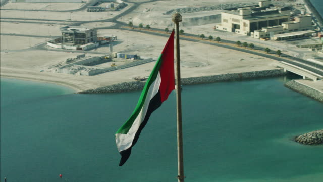 aerial uae national flag flying port dubai creek - vereinigte arabische emirate stock-videos und b-roll-filmmaterial