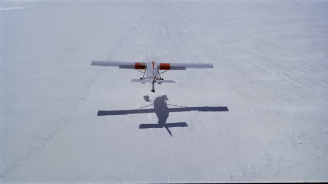 Aerial upper-winged plane landing on snowcovered field / New Zealand