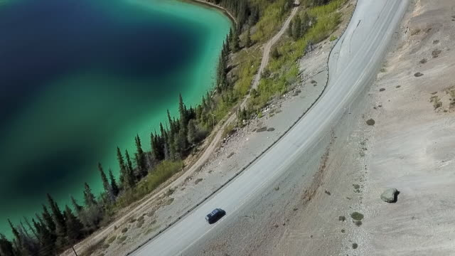 aerial: van driving alongside a lake - next to stock videos and b-roll footage