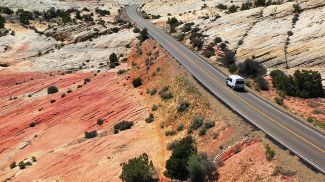 aerial: van moving on highway at grand staircase-escalante national monument, vehicle on road in desert - グランドステアケースエスカランテ国定公園点の映像素材/bロール