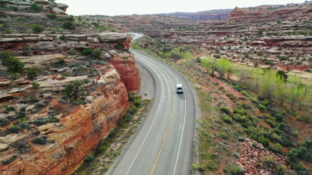 aerial: van moving over winding road by rock formation at canyonlands national park - canyonlands national park stock videos & royalty-free footage