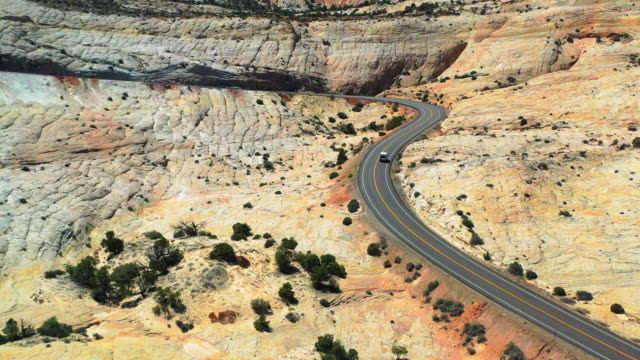 aerial: vehicle moving on highway at grand staircase-escalante national monument, van on road in desert - グランドステアケースエスカランテ国定公園点の映像素材/bロール