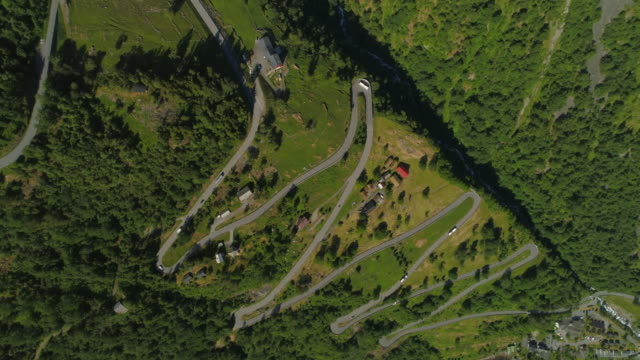 aerial: vehicle traveling on winding road amidst greenery on mountain with houses during sunny day - geiranger fjord, norway - zigzag stock videos & royalty-free footage