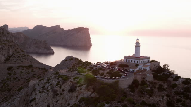 aerial: vehicles on winding road by lighthouse at cap de formentor against sky, scenic view of sea and mountains during sunset - mallorca, spain - majorca stock videos & royalty-free footage