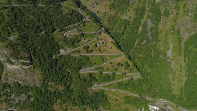 aerial: vehicles traveling along winding road amidst greenery on mountain - geiranger fjord, norway - ジグザグ点の映像素材/bロール