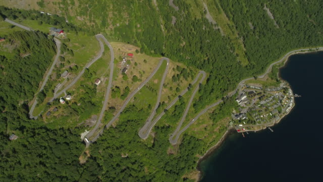 aerial: vehicles traveling on zigzag winding road amidst green mountain by fjord - geiranger fjord, norway - zigzag stock videos & royalty-free footage