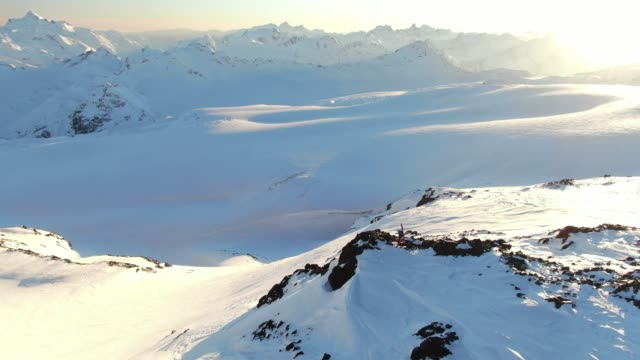 雪の山の端にスキーヤーの空中垂直ドローンショット - 辺縁部点の映像素材/bロール