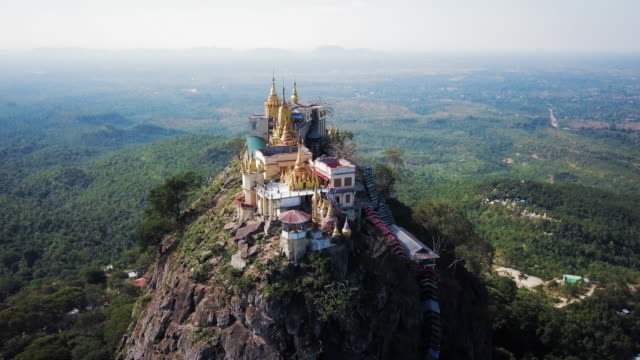 aerial: vibrant colors and gold steeples of popa taungkalat - buddhismus stock-videos und b-roll-filmmaterial