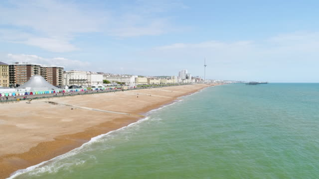 4k aerial video brighton promenade flying low along beach and surf - brighton england stock videos and b-roll footage