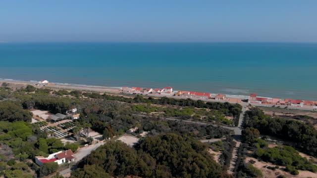 vídeos y material grabado en eventos de stock de aerial video camera moves from pine forest to the beach mediterranean sea of guardamar del segura - pinar