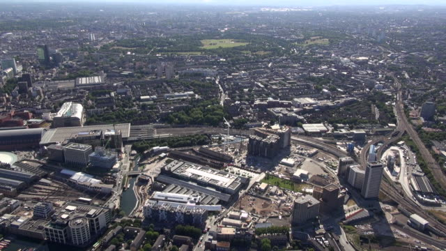 Aerial video close-up of Kings Cross Central building development site looking westwards, with Regents Canal, Kings Place and St Pancras International Station and views over Regent's park