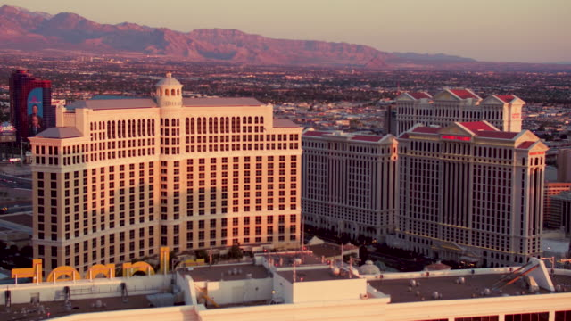 Aerial video flying around top of Planet Hollywood Resort & Casino, view of the Bellagio, sunrise