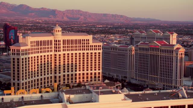vídeos y material grabado en eventos de stock de aerial video flying around top of planet hollywood resort & casino, view of the bellagio, sunrise - caesars palace las vegas
