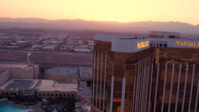 aerial video flying close to mandalay bay hotel and casino, sunset - mandalay stock videos and b-roll footage