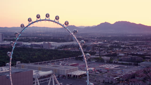 aerial video flying over las vegas around ferris wheel of high roller, sunset - the mirage las vegas stock videos & royalty-free footage