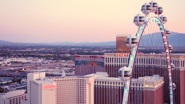 vídeos y material grabado en eventos de stock de aerial video flying over las vegas around ferris wheel of high roller, sunset - hotel mirage las vegas