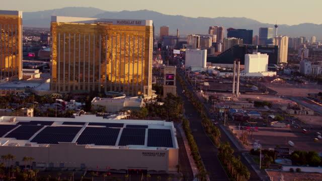 vídeos y material grabado en eventos de stock de aerial video flying over the las vegas strip, around hotels & casinos, sunrise - mandalay bay resort & casino