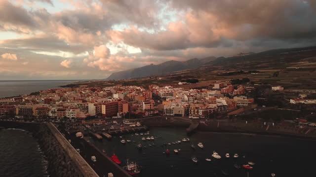 aerial video flying over the ocean towards the town of playa san juan, santa cruz de tenerife in the canary islands, spain, at sunset - pier stock videos & royalty-free footage