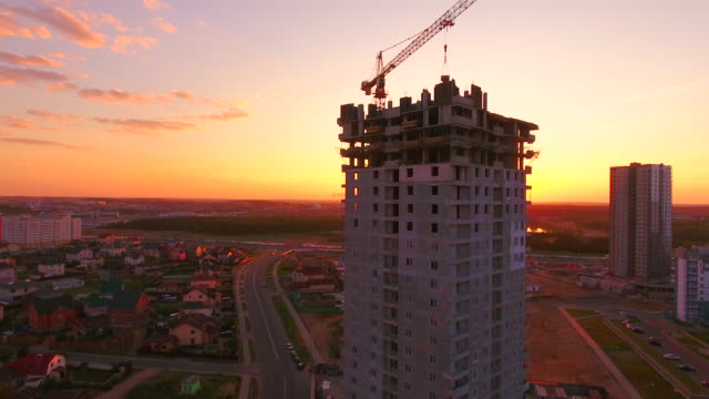 Aerial video footage of construction cranes at construction site