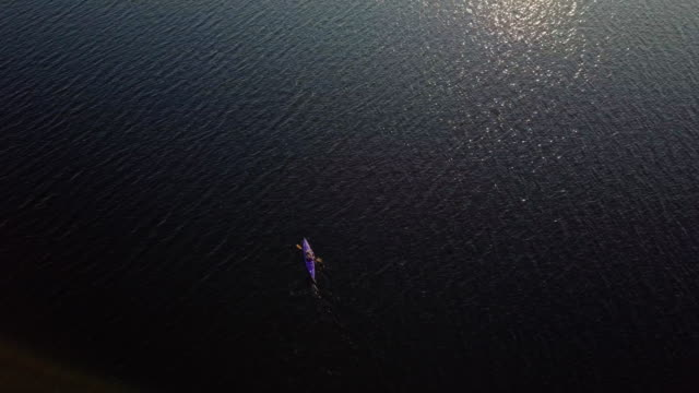 4k aerial video healthy woman kayaking at sunrise on lake - infinity stock videos & royalty-free footage