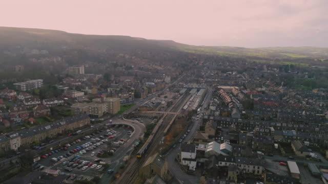 aerial video ilkley west yorkshire train arriving at dusk - スキップトン点の映像素材/bロール