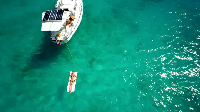 aerial video of a sloop anchored in the caribbean bay - yacht stock videos & royalty-free footage