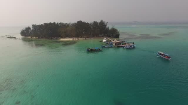 vídeos y material grabado en eventos de stock de aerial video of a wooden boat near a pier on a small island flying backwards - yakarta