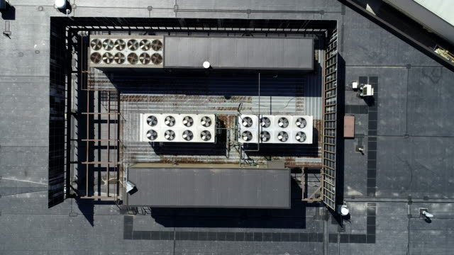 aerial video of air conditioning fans spinning on commercial building - klimaanlage stock-videos und b-roll-filmmaterial