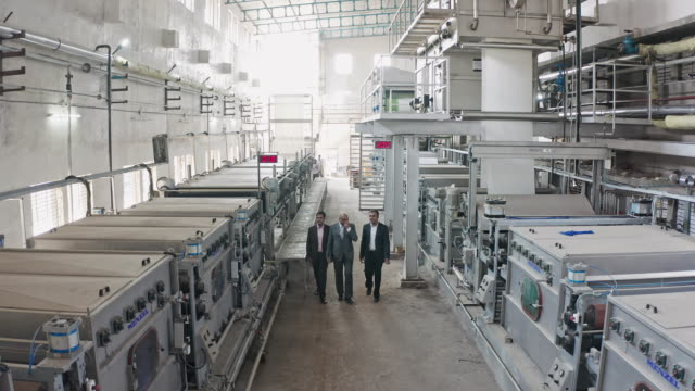 aerial video of ceo indian businessman walking with his factory managers at factory - officina video stock e b–roll