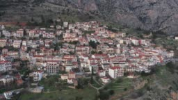 Aerial video of Delphi, Greece, orange colors, mountainside with layered hills beyond with rooftops in foreground