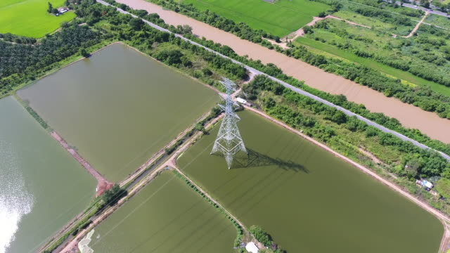 Aerial Video of High Voltage Electricity Tower Standing on Rice Paddy in Rural Area