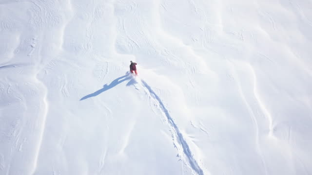 4k uhd aerial video of man snowshoeing in fresh powder snow - track imprint stock videos and b-roll footage