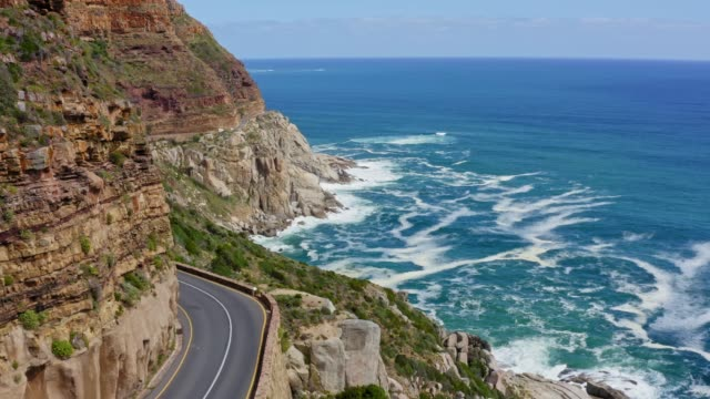 aerial video of winding road at chapman's peak drive - cliff stock videos & royalty-free footage