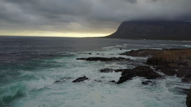 Aerial video over a rocky coastline into the sunset